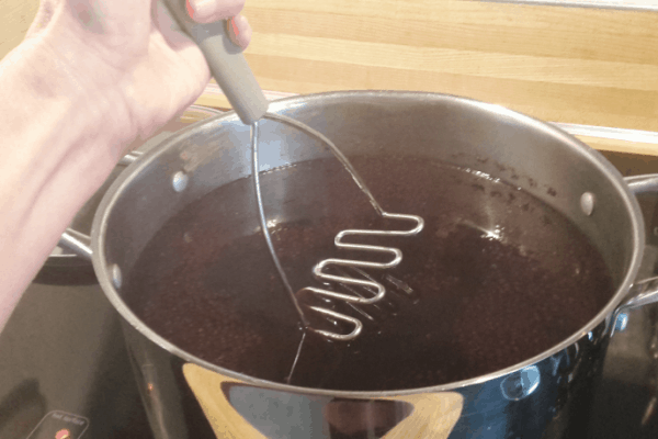 mashing elderberries for syrup